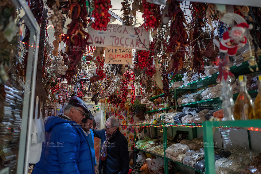 Italy. Apulia Region. Gravina in Puglia. A shop owner(C) with two customers inside the small shop which sells dry seeds, garlic plaits, dried mushrooms and chili red peppers. The chili pepper is the fruit of plants belonging to the members of the family Solanaceae. About thirty species exist as shrubs with brightly colored, mostly spicy, fruits. Chili peppers are widely used in many cuisines to add spiciness to dishes. The substances that give chili peppers their pungency when ingested or applied topically are capsaicin and related capsaicinoids. Gravina in Puglia is a town in Apulia (Puglia) which is a region in Southern Italy. 8.12.18  © 2018 Didier Ruef
