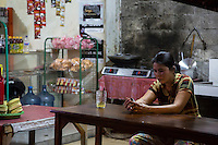Jimbaran, Bali, Indonesia.  Woman Checking her Cell Phone at a Nighttime Refreshment Shop.
