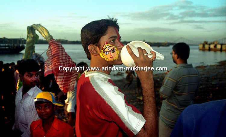 INDIA (West Bengal - Calcutta)  2006, A boy with a tatto of Durga on his face blows up a shell during the immerssion ritual of Durga.  Its a ritual of drowning the idol on the fifth day in the Ganges after the worship is over. Durga Puja Festival is the biggest festival among bengalies.  As Calcutta is the capital of West Bengal and cultural hub of  the bengali community Durga puja is held with the maximum pomp and vigour. Ritualistic worship, food, drink, new clothes, visiting friends and relatives places and merryment is a part of it. In this festival the hindus worship a ten handed godess riding on a lion armed wth all possible deadly ancient weapons along with her 4 children (Ganesha - God for sucess, Saraswati - Goddess for arts and education, Laxmi - Goddess of wealth and prosperity, Kartikeya - The god of manly hood and beauty). Durga is symbolised as the women power in Indian Mythology.  In Calcutta people from all the religions enjoy these four days of festival in the moth of October. Now the religious festival has become the biggest cultural extravagenza of Calcutta the cultural capital of India. Artistry and craftsmanship can be seen in different sizes and shapes in form of the idol, the interior decor and as well as the pandals erected on the streets, roads and  parks.- Arindam Mukherjee