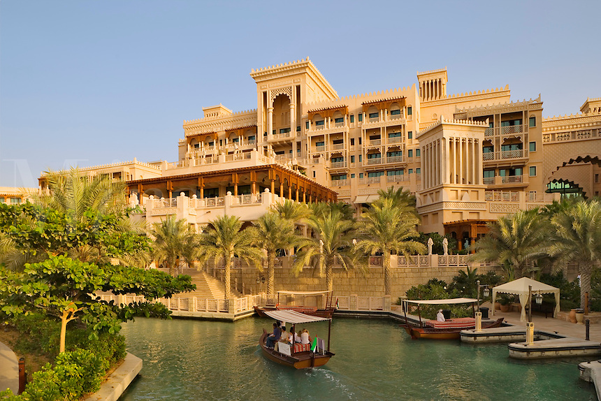 Dubai.  Al Qasr Hotel, built in the style of a Moroccan palace, seen over one of the Madinat Jumeirah?s canals with an abra, a water taxi.