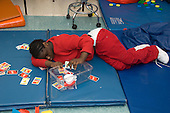 MR / Albany, NY.Langan School at Center for Disability Services .Ungraded private school which serves individuals with multiple disabilities.Child lies on mat and places game cards in plastic container while she plays. Student is wearing a diaper. Like some people with cerebral palsy, her muscles are not capable of allowing her to manage her toileting independently. Girl: 10, African-American, cerebral palsy, expressive and receptive language delays.MR: And6.© Ellen B. Senisi