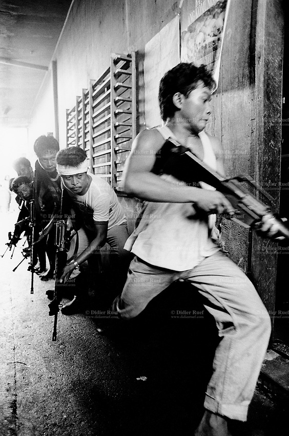 Philippines. Luzon Region. Manila. Tondo area. Smokey mountain is a rubbish dump. Life on a garbage heap. As a goal to help the people to fight the violence, the army, with 50 persons from the special operations forces always present on Smokey Mountain, train every saturday some volunters, all inhabitants, to the basic rules of street war fightings. Military exercice with M16 (more formally United States Rifle, Caliber 5.56 mm, M16). The automatic machine guns do not have any bullets. © 1992 Didier Ruef .