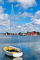 Sailboat in Mystic harbor looking torward the Mystic Seaport Museum, Mystic, Ct, USA