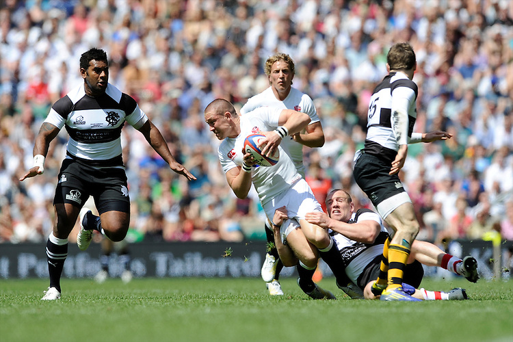 Mike Brown of England is tackled by Mike Tindall of the Barbarians during the match between England and Barbarians at Twickenham on Sunday 26th May 2013 (Photo by Rob Munro)