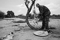 North Darfur, August 13, 2004.Janjaweed militiaman preparing a 'mechoui'