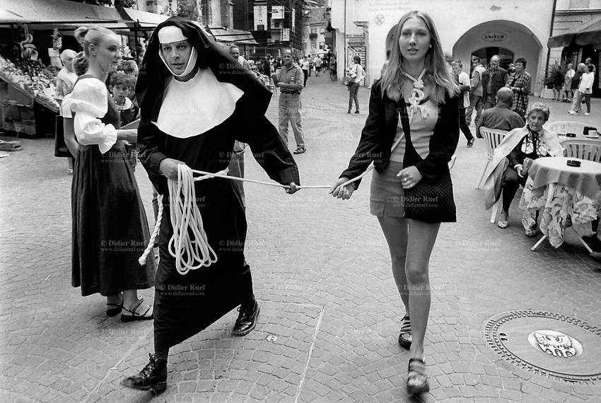 Italy. South Tyrol. Meran. A man dressed as a nun holds a rope in his hand and walks in the town center pulling a woman with noose around her neck. Meran (in italian Merano) is a town and comune in South Tyrol. South Tyrol (German: Südtirol; Italian: Sudtirolo, also known by its alternative Italian name Alto Adige) is an autonomous province in northern Italy. 10.08.1999 © 1999 Didier Ruef