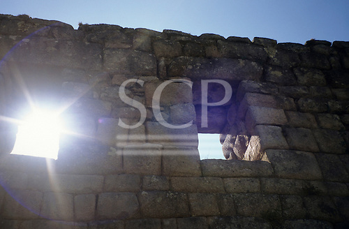 """Machu Picchu, Peru. View up at Inca wall in """"Lost City of Incas"""" with windows and sunburst in one window."""