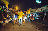 A man is seen with two prostitutes on a side street off Fields Avenue, the main strip of bars offering cheap prostitutes that runs through Angeles City, Republic of the Philippines, 08 November 2014. The 'sin city', which sprung up on the fringes of a US Air Force base during the Vietnam war, has a reputation for cheap sex, and was a favourite destination for alleged murderer Rurik Jutting, who used to fly to Angeles City from Hong Kong for debauched weekends. The British banker is currently on remand at a secure facility in Hong Kong for allegedly murdering two Indonesian prostitutes in his flat whilst high on alcohol and cocaine.