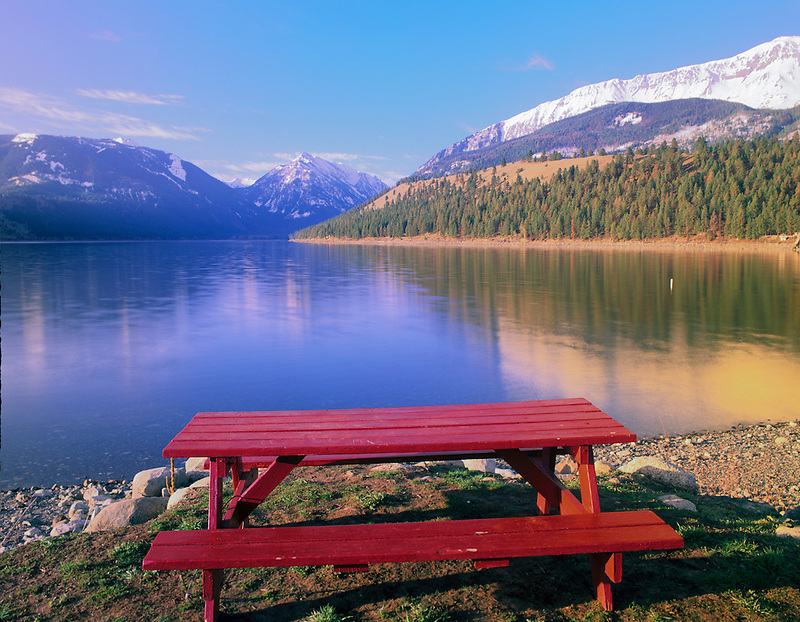 Red picnic table on shore of Wallowa Lake with Wallowa Mountains. Oregon