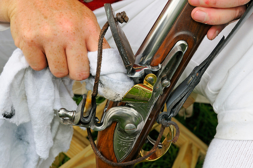 British soldier cleans the pan of his short land pattern flintlock musket, marked Grice 1762 with golden GR flash guard,  reproduced by Pedersoli , during a re-enactment of the 1775 Siege of Boston, Boston Common, Massachusetts, USA.