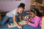 Education preschool 4 year olds two girls playing with dolls and blocks creating enviroment