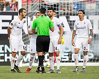 Fiorentina players discuss the Arsenal goal with the referee