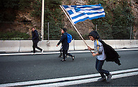 Pictured: A young migrant walks on the motorway with a greek flag Thursday 25 February 2016<br />Re: Hundreds of migrants, including families with young children, that were stranded at Tempe in central Greece, were forced to walk on foot on the motorway to reach Idomen, about 168 kilometres away, in the northern part of the country, at the Greek FYRO Macedonian border. Local police were at first escorting them, then made sure that they were safely transported on coaches.
