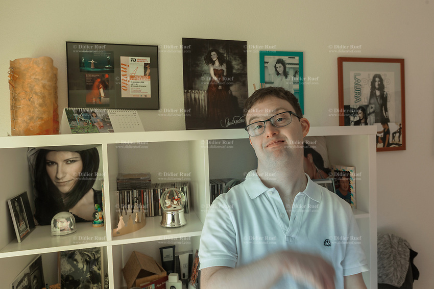 Switzerland. Canton Ticino. Gordola. Simone Lunardi stands in his bedroom with posters and records of his favorite Italian singer, Laura Pausini. Simone Lunardi is a dancing member of MOPS_DanceSyndrome which is an independent Swiss artistic, cultural and social organisation operating in the field of contemporary dance and disability. It is composed only of Down dancers. Down syndrome (DS or DNS), also known as trisomy 21, is a genetic disorder caused by the presence of all or part of a third copy of chromosome 21 It is usually associated with physical growth delays, mild to moderate intellectual disability, and characteristic facial features. Laura Pausini  (born 16 May 1974) is an Italian pop singer-songwriter, record producer and television personality. She is an international success musician selling millions of records. Gordola is a municipality in the district of Locarno. 31.01.2020 © 2020 Didier Ruef