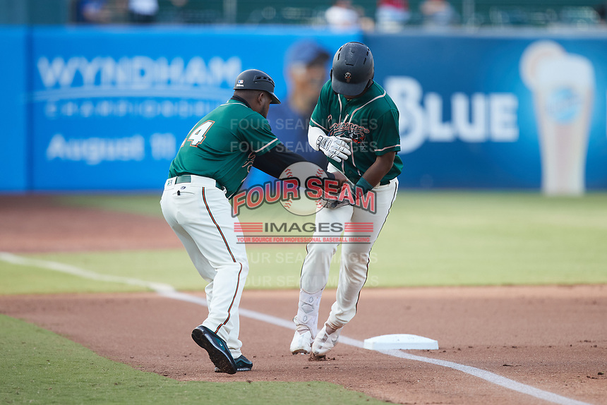 Greensboro Grasshoppers manager Kieran Mattison (24) fakes a hand-off to Matthew Fraizer (14) as he rounds third base after hitting a home run against the Winston-Salem Dash at First National Bank Field on June 3, 2021 in Greensboro, North Carolina. (Brian Westerholt/Four Seam Images)