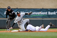 Furman's Hunter Burton (1) slides safely into third with a stolen base as the ball skips past third baseman AJ Mackey (13) of USC Upstate in the third inning of a game on Tuesday, March 4, 2014, at Fluor Field at the West End in Greenville, South Carolina. (Tom Priddy/Four Seam Images)
