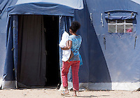 Migranti nella tendopoli allestita presso la stazione Tiburtina a Roma, 16 giugno 2015.<br /> A woman keeping a child in her arms enters a tent in the camp set up near the Tiburtina railway station in Rome, 15 June 2015. Italy is facing a huge flow of migrants brought to Sicily after rescue at sea, many of whom are trying to join their relatives in northern Europe. <br /> UPDATE IMAGES PRESS/Riccardo De Luca