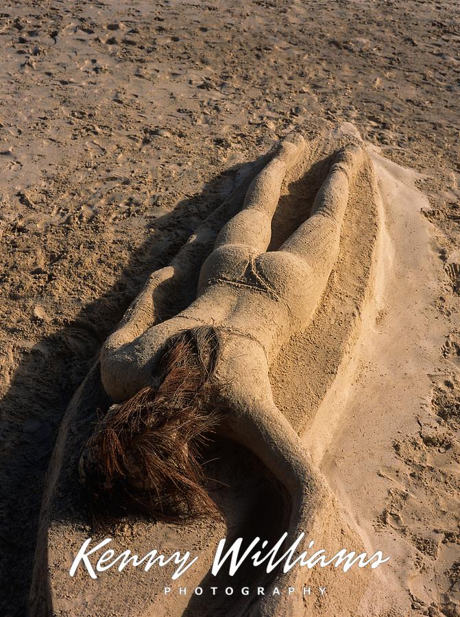 Surfer Girl Laying on Surfboard Sand Sculpture, Kailua Beach Park, Oahu, Hawaii, USA.