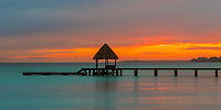 Colorful twilight on pier with a thatched roof on the turquoise lagoon water, in Rangiroa Tuamotus atoll, French Polynesia, South Pacific Ocean