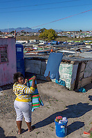 South Africa, Cape Town, Khayelitsha Township.  Woman Hanging her Laundry.
