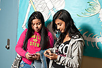 High school two girls checking cell phones between classes.