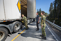 Home Guard soldier Thore Rinden checking a truck, with Kristian Moen looking on. Norwegian authorites introduced strict measures to combat the Coronavirus (COVID-19) in March 2020. This included closing the borders, and any Norwegians returning from abroad is given two weeks quarantine. <br /> <br /> Police and soldiers from the Home Guard of the Army (Heimevernet) man checkpoints along side roads and regular border crossings to enforce the travel restrictions.<br /> <br /> <br /> <br /> ©Fredrik Naumann/Felix Features