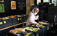 Nederland - Amsterdam - Oktober 2020.    Voedselbank. Uitgiftepunt Noord Banne Buikslootlaan. De voedselbank verzorgt pakketen voor mensen met een minimuminkomen. Een medewerkster vult de dozen.   Foto mag niet in negatieve / schadelijke context gepubliceerd worden.   Foto : ANP/ HH / Berlinda van Dam