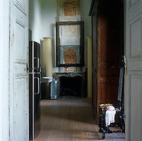 Distressed double doors open onto a utility room where a contemporary black fridge stands opposite a large armoire and a picture-less frame hangs above the marble fireplace