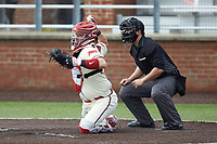 Dayton Flyers catcher Jay Curtis (10) makes a throw to third base as home plate umpire Cody Clark looks on during the game against the Campbell Camels at Jim Perry Stadium on February 28, 2021 in Buies Creek, North Carolina. The Camels defeated the Flyers 11-2. (Brian Westerholt/Four Seam Images)