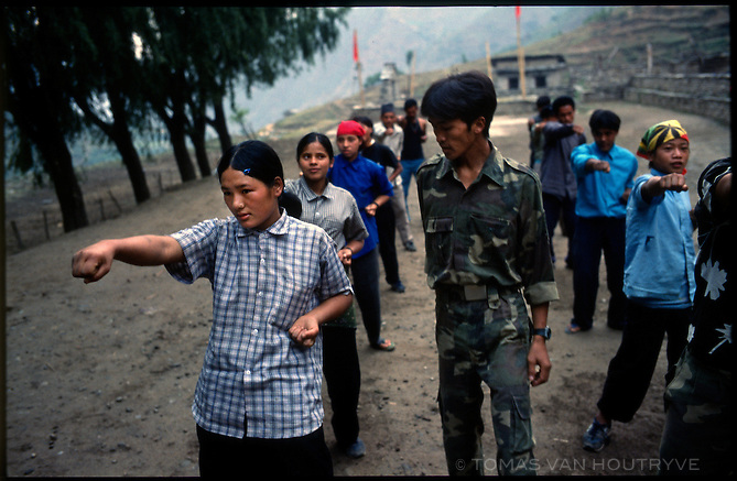 Comrade Mukti, a commander in the Maoist People's Liberation Army, leads children in military style physical training in Thabang, the capital of Nepal's Maoist held areas on Tuesday, 21 June 2005. The Maoist rebels have built a school near Thabang where they teach students according to a Marxist inspired curiculum.<br />