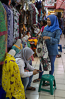Yogyakarta, Java, Indonesia.  Young Woman Shopping for Clothes, another Checking Cell Phone.  Beringharjo Market.