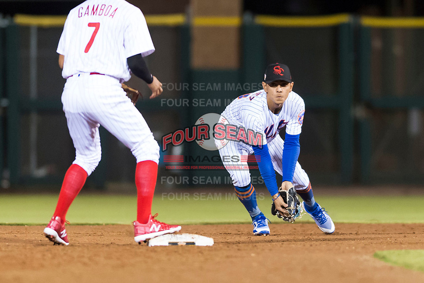 Scottsdale Scorpions second baseman Andres Gimenez (13), of the New York Mets organization, prepares to flip a ball to shortstop Arquimedes Gamboa (7), of the Philadelphia Phillies organization, to start a double play during an Arizona Fall League game against the Surprise Saguaros at Scottsdale Stadium on October 15, 2018 in Scottsdale, Arizona. Surprise defeated Scottsdale 2-0. (Zachary Lucy/Four Seam Images)