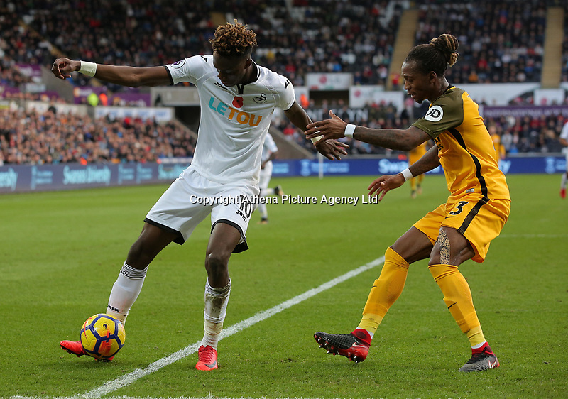 (L-R) Tammy Abraham of Swansea City challenged by Gaetan Bong of Brighton during the Premier League match between Swansea City and Brighton and Hove Albion at The Liberty Stadium, Swansea, Wales, UK. Saturday 04 November 2017