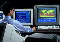 Computer technician sitting at computers showing Space Shuttle software. Computer technician. Houston Texas.