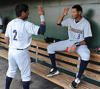 Infielder Cito Culver (2) of the Charleston RiverDogs, left, salutes teammate outfielder Mason Williams (9) in the dugout just before a game against the Greenville Drive on May 31, 2012, at Fluor Field at the West End in Greenville, South Carolina. Charleston won, 13-2.  (Tom Priddy/Four Seam Images)