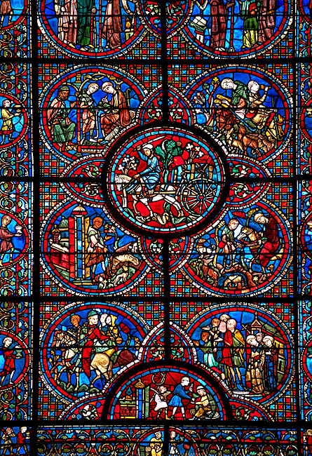 Medieval stained glass Window of the Gothic Cathedral of Chartres, France - dedicated to the Life of St Lubin . Central panel shows A barrel of wine being transported to the Cathedral, below left - The young Lubin working as a shepherd, below right - A monk gives Lubin a belt with the alphabet written on it, above left - Lubin receiving instruction from a cleric, above right - Lubin spends his spare time learning to read, while his companion idles.  Cental bottom semi circle - wine cryers, above left -a procession, above right - a procession of laymen and clerics.  A UNESCO World Heritage Site..