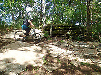 Suzanne Schmidt heads into a tight, rocky turn June 11 2021 on the Marble Flats trails. <br />(NWA Democrat-Gazette/Flip Putthoff)