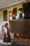 Germany, Baden-Wurttemberg, Kirnbach (Wolfach): three young women in famous Black Forest costume with red and black Bollenhat and an original Black Forest farmhouse | Deutschland, Baden-Wuerttemberg, Ortenaukreis, Kirnbach (Wolfach): drei junge Frauen an einem echten Schwarzwaelder Bauernhaus in der beruehmten Kirnbacher Tracht mit dem roten und schwarzen Bollenhut, die heute in der ganzen Welt als Schwarzwaelder Tracht bekannt ist