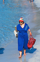 Spain. Mallorca in the Balearic islands. Colonia Sant Jordi. A swiss woman, a tourist, walks on the beach bare feet and carries in her hand her shoes and a bag. She wears on her head a hat with a swiss flag. © 1999 Didier Ruef