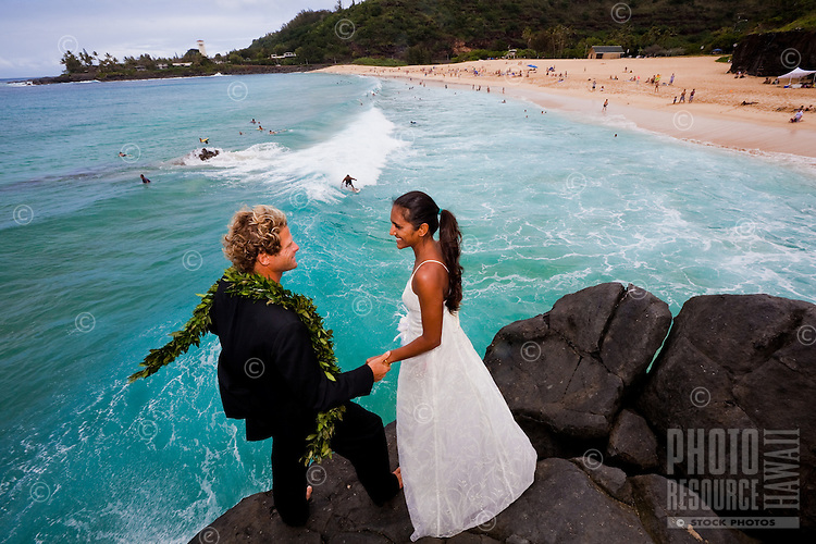 Couple in wedding attire holding hands on the Waimea jump rock before jumping off together