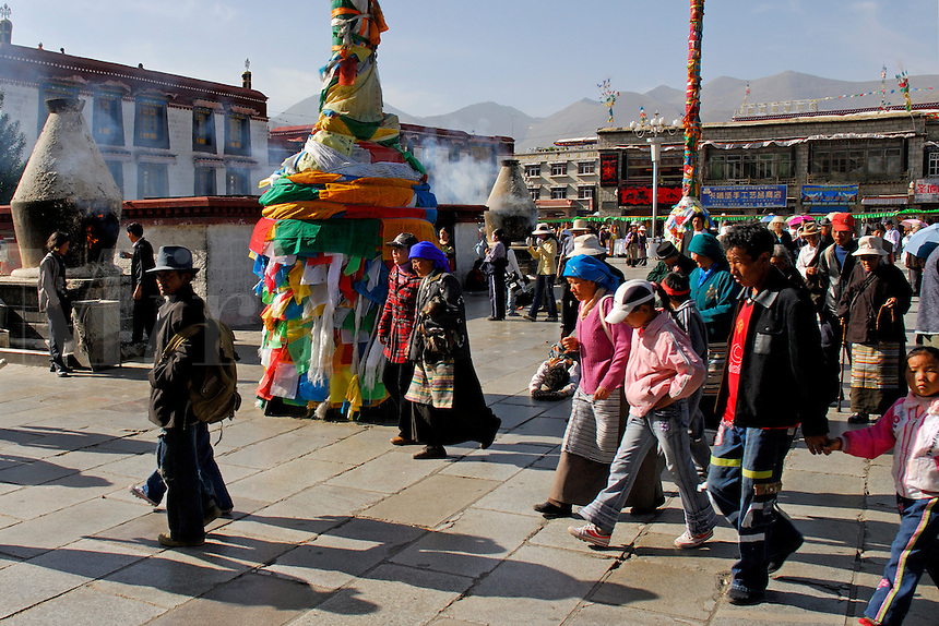 Buddhists circumambulating the Barkhor pilgrim circuit in front of the Jokhang Temple, with prayer-flag poles and incense burners, during the Saga Dawa festival, Lhasa, Tibet.