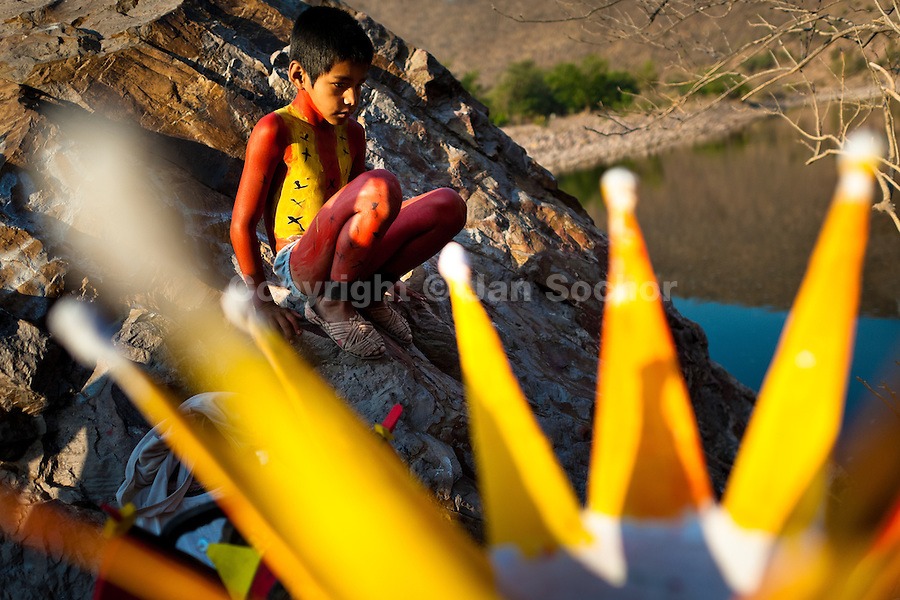 """A Cora Indian boy, with body painted all over in red color, sits on a rock before the religious ritual celebration of Semana Santa (Holy Week) in Jesús María, Nayarit, Mexico, 22 April 2011. The annual week-long Easter festivity (called """"La Judea""""), performed in the rugged mountain country of Sierra del Nayar, merges indigenous tradition (agricultural cycle and the regeneration of life worshipping) and animistic beliefs with the Christian dogma. Each year in the spring, the Cora villages are taken over by hundreds of wildly running men. Painted all over their semi-naked bodies, fighting ritual battles with wooden swords and dancing crazily, they perform demons (the evil) that metaphorically chase Jesus Christ, kill him, but finally fail due to his resurrection. La Judea, the Holy Week sacred spectacle, represents the most truthful expression of the Coras' culture, religiosity and identity."""