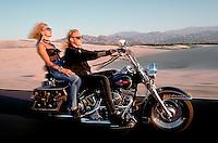 Man and woman riding through the California desert on a Harley  Davidson