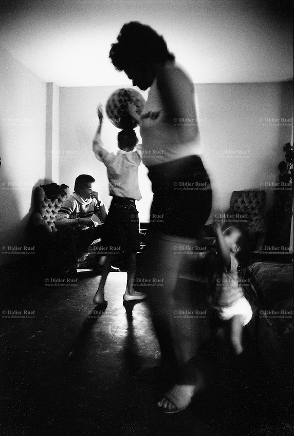"""USA. New York City. Spanish Harlem. Puerto Rican family. Party in the evening. The mother Nina dances with her son Papo and her daughter Sala holding a balloon on her head. Her son carlos seats on a sofa. The family lives below the poverty line and receives public assistance (AFDC, Home Relief, Supplemental Security Income and Medicaid). The family resides in units managed by the New York City Housing Authority (NYCHA) which provides housing for low income residents. NYCHA administers rental apartments in facilities, popularly known as """"projects"""". Spanish Harlem, also known as El Barrio and East Harlem, is a low income neighborhood in Harlem area. Spanish Harlem is one of the largest predominantly Latino communities in New York City. 15.04.86 © 1986 Didier Ruef .."""