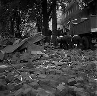 Square Charles de Gaulle, rue du Poids-de-l'Huile. 12 juin 1968. Vue d'ensemble déblayage des barricades : au 1er plan amas de pavés et de bois ; en arrière-plan trois hommes de dos ramassent des morceaux de pierre, d'autres hommes regardent la scène, camion de la ville de Toulouse stationné. Cliché pris durant les évènements de Mai 68 à Toulouse