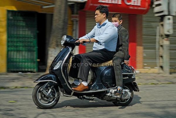 Asia, Vietnam, Hanoi. Hanoi old quarter. Father and son with face mask on black Vespa motorbike rushing through Hanoi.