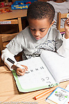 Education preschool 3-4 year olds boy writing letters with marker