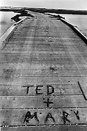 """July 19th 1969, Chappaquiddick, Edgartown, Martha's Vineyard, Massachusetts,<br /> The Dike wooden bridge on Poucha Pond on Chappaquiddick Island in 1969 with """"Ted + Mary"""" written on it. The site is where aide Mary Jo Kopechne was killed in an car accident when Senator Edward Kennedy was driving."""