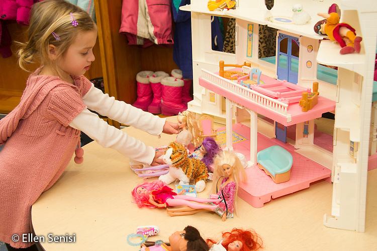 MR / Schenectady, NY. Zoller Elementary School (urban public school). Kindergarten inclusion classroom. Student (girl, 5) plays with dolls and dollhouse at free playtime. MR: Bog2. ID: AM-gKw. © Ellen B. Senisi.