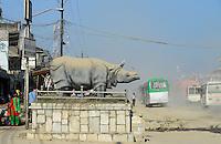 NEPAL, Terai, Chitwan Nationalpark, town Tandi, Rhino sculpture and damaged road with dust / Nepal, Terai, Chitwan Nationalpark, Stadt Tandi, Nashorn Skulptur und kaputte Strasse mit viel Staub
